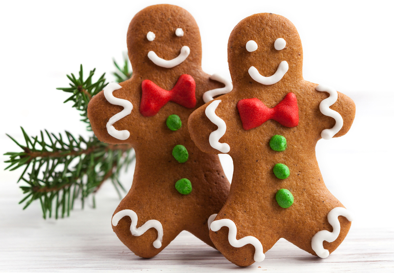 stock-photo-smiling-gingerbread-men-on-white-wooden-background-214626889